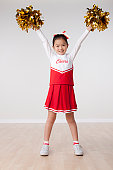 Studio portrait of girl (8-9) cheerleading