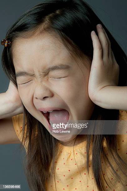 Studio portrait of girl (8-9) covering ears and screaming