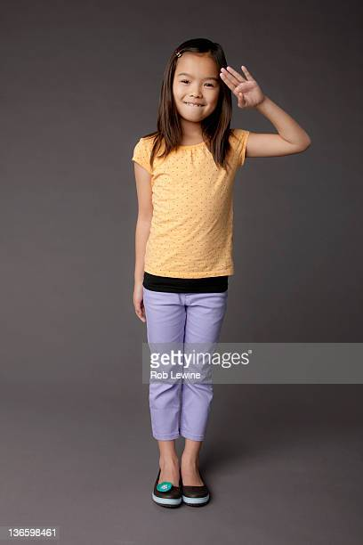 Studio portrait of girl (8-9) saluting
