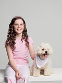 Studio portrait of girl (8-9 years) sitting with West Highland Terrier