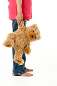 Studio Portrait of Girl Standing with Teddy Bear
