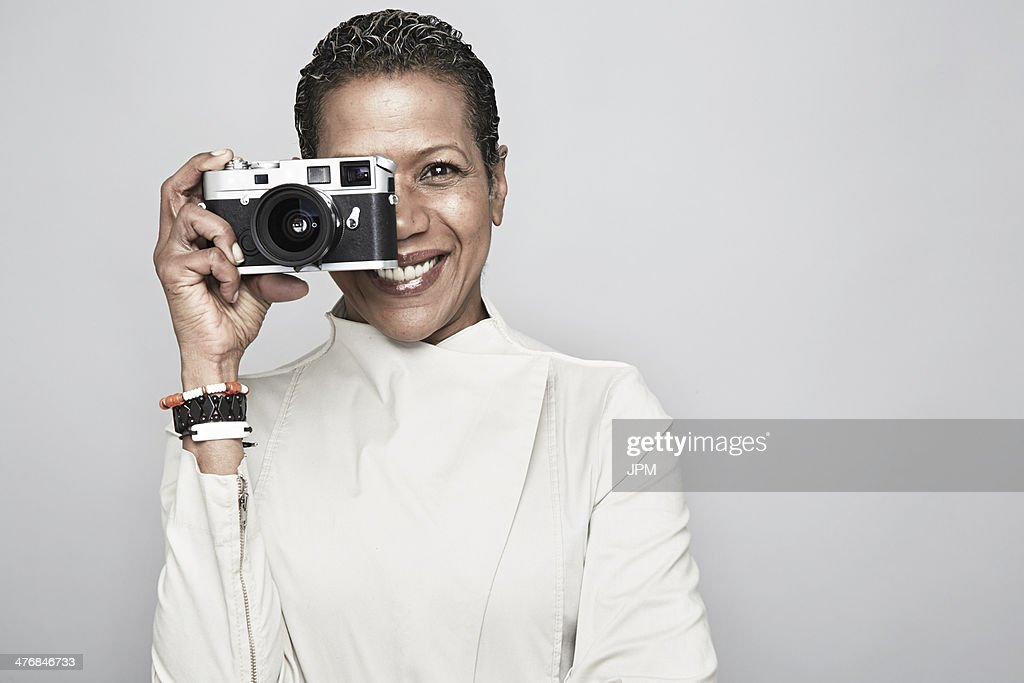 Studio portrait of happy mature woman holding up camera