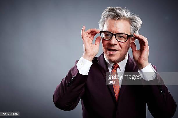 Studio portrait of mature businessman adjusting his spectacles