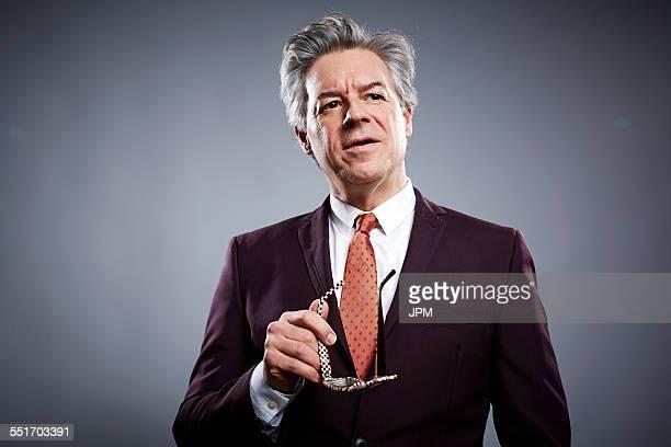 Studio portrait of mature businessman holding his spectacles
