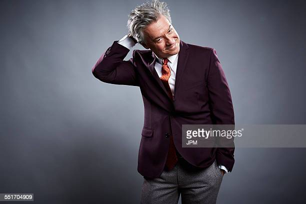 Studio portrait of mature businessman scratching his head