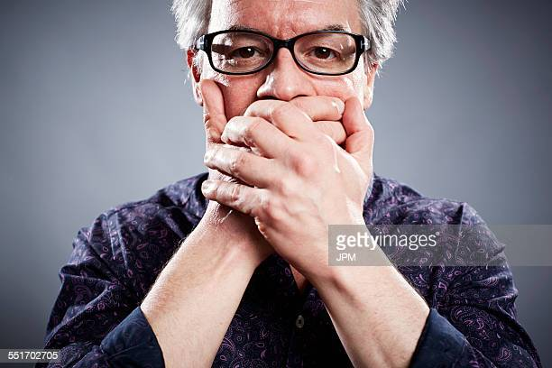 Studio portrait of mature businessman with hands covering mouth