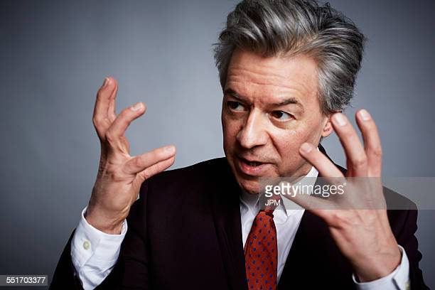 Studio portrait of mature businessman with hands open in explanation