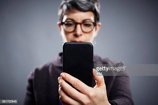 Studio portrait of mature businesswoman reading smartphone