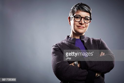 Studio portrait of mature businesswoman with arms folded