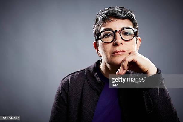 Studio portrait of mature businesswoman with chin on hand
