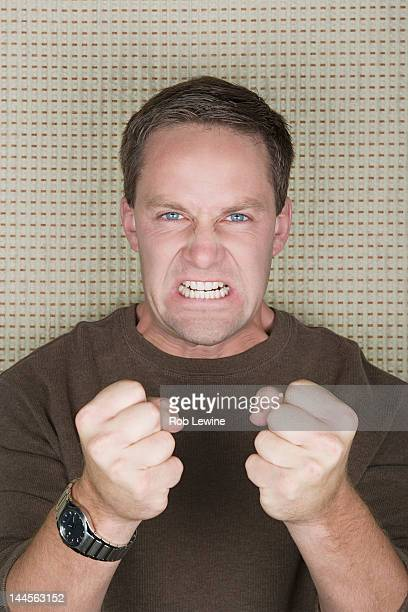 Studio portrait of mature man clenching teeth and fists
