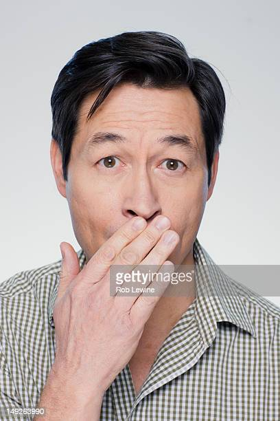 Studio portrait of mature man covering mouth