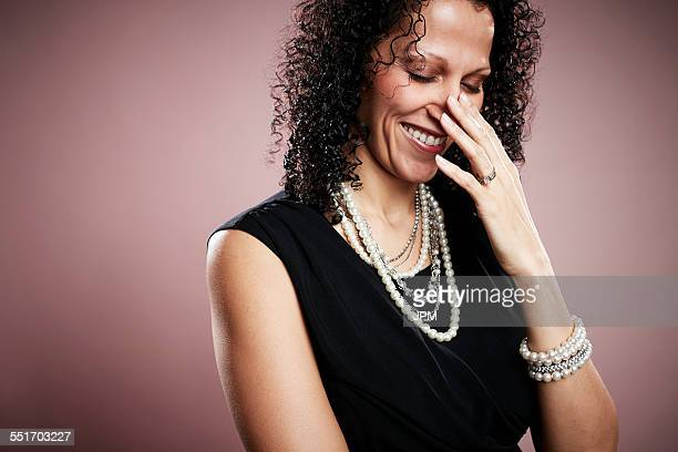 Studio portrait of mature woman with hand on face giggling