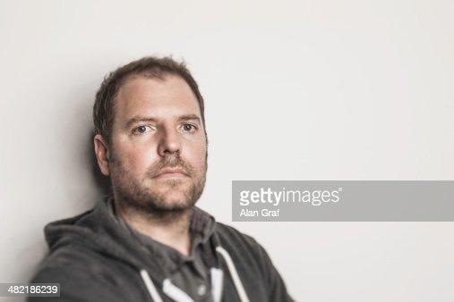 Studio portrait of mid adult man in hooded top