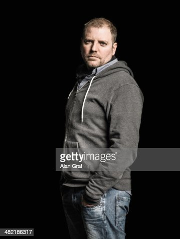 Studio portrait of mid adult man with hands in pockets : Stock Photo