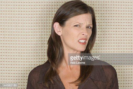 Studio portrait of mid adult woman grimacing