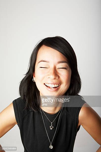 Studio portrait of mid adult woman laughing with eyes closed