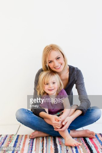 Studio portrait of mother and young daughter on rug