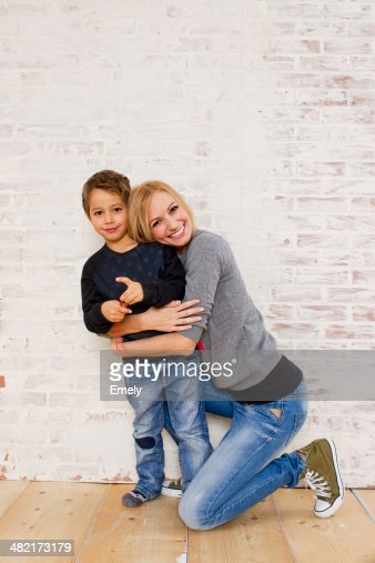 Studio portrait of mother kneeling next to son