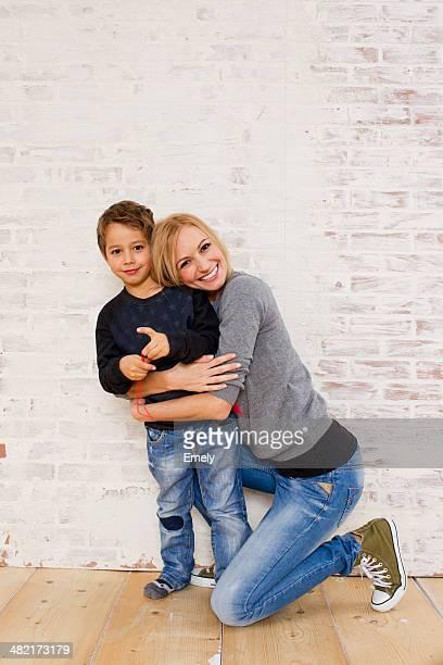 Studio portrait of mother kneeling next to son