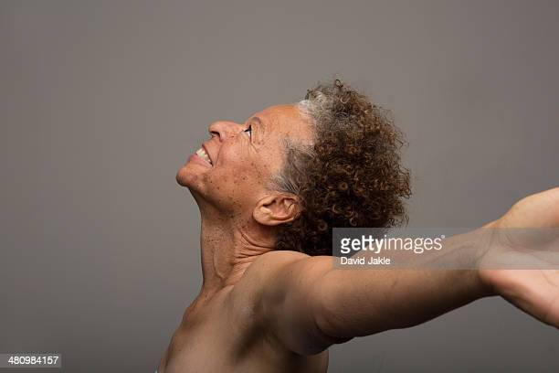 Studio portrait of nude senior woman with arms outstretched