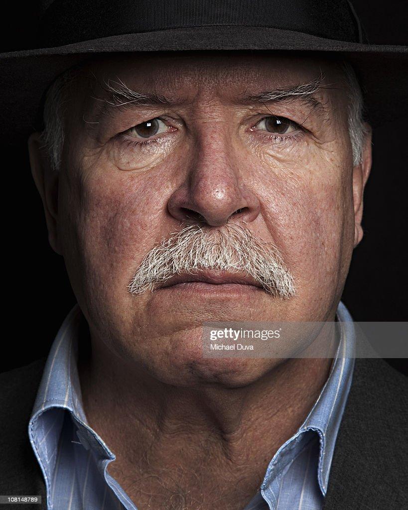studio portrait of older man black background : Stock Photo