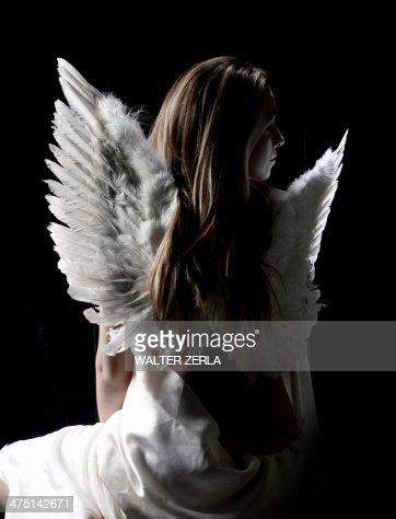 Studio portrait of pensive woman wearing angel wings