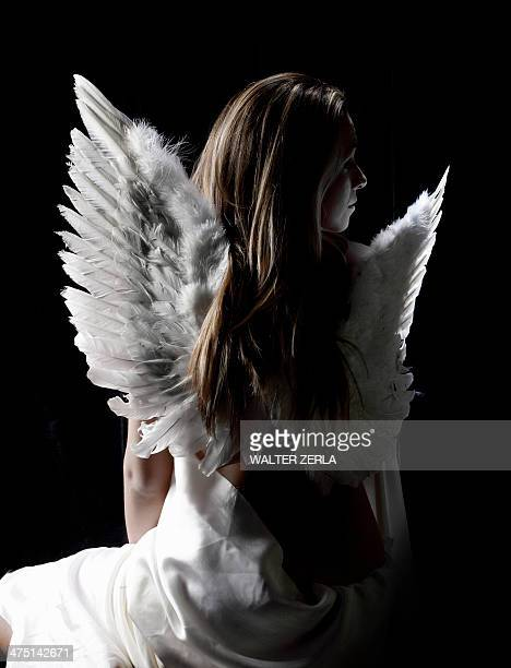 Studio portrait of pensive woman wearing angel wings