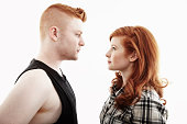 Studio portrait of red haired young couple gazing face to face