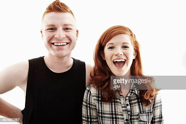 Studio portrait of red haired young couple laughing