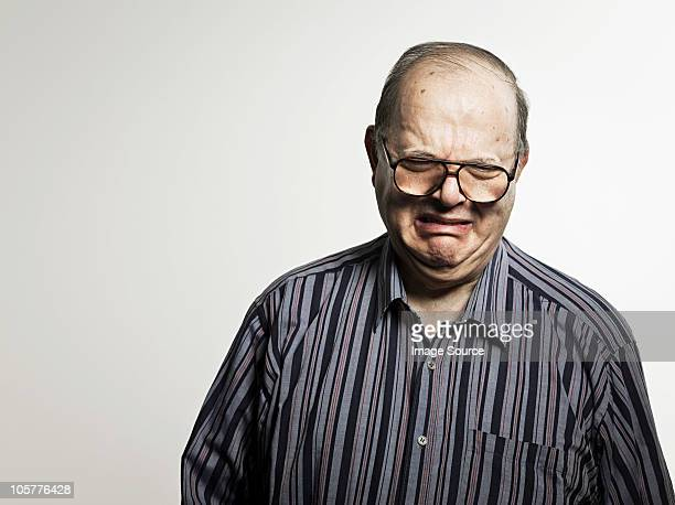 Studio portrait of sad senior man crying