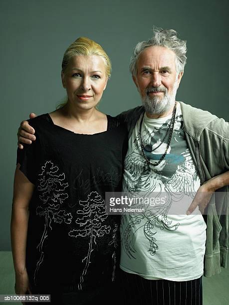 Studio portrait of senior man with arm around mature woman,