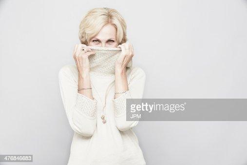 Studio portrait of senior woman hiding behind roll neck