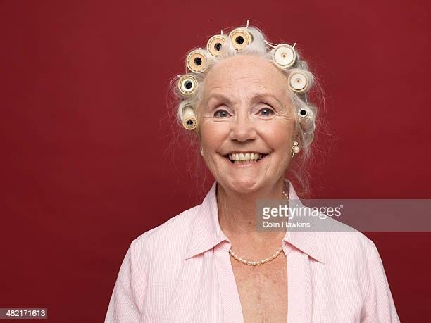 Studio portrait of senior woman in hair rollers