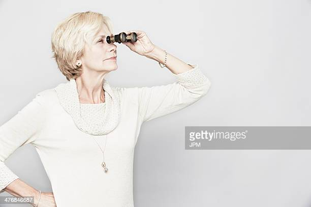 Studio portrait of senior woman looking through binoculars