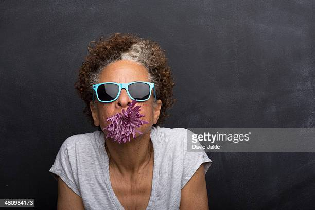 Studio portrait of senior woman with flower in her mouth