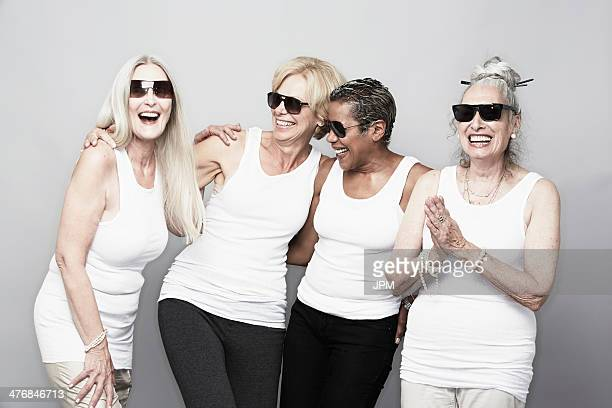 Studio portrait of senior women friends in sunglasses