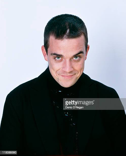 A studio portrait of singer songwriter Robbie Williams dressed in black circa 1998