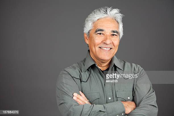 Studio portrait of smiling hispanic mature man with grey hair