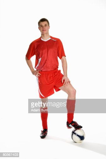 Studio portrait of soccer player with his foot on a soccer ball