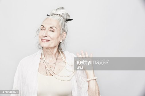 Studio portrait of sophisticated senior woman holding beads