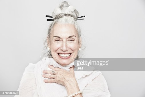 Studio portrait of sophisticated senior woman laughing