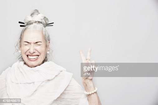 Studio portrait of sophisticated senior woman making victory sign