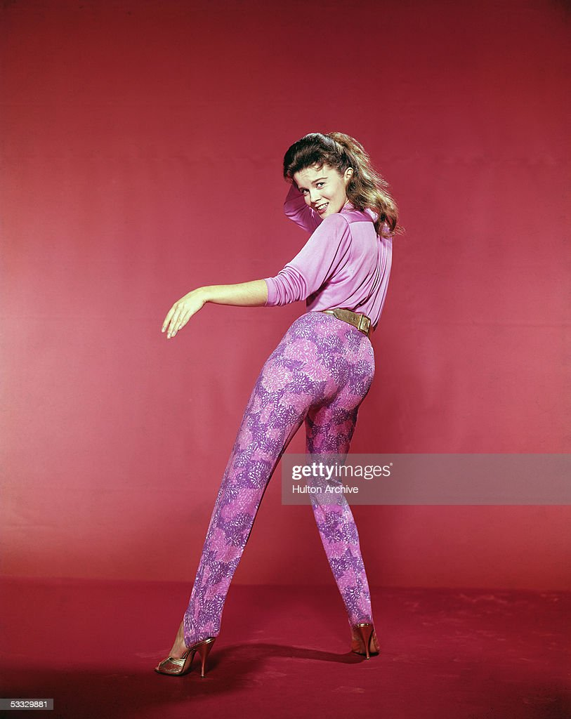 Studio portrait of Swedishborn actress and dancer AnnMargret wear a blouse leggings and high heels dancing while looking over her shoulder at the...