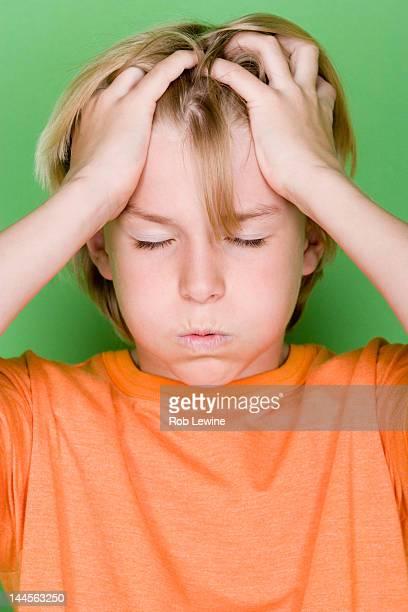 Studio portrait of teenage (16-17) boy with head in hands