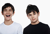 Studio portrait of twin boys (13-15), one laughing