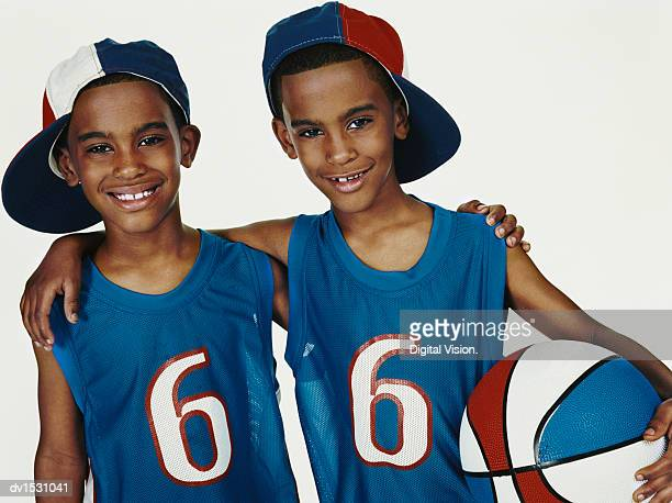 Studio Portrait of Twin Brothers in Sports Strips With Arms Around Each Other