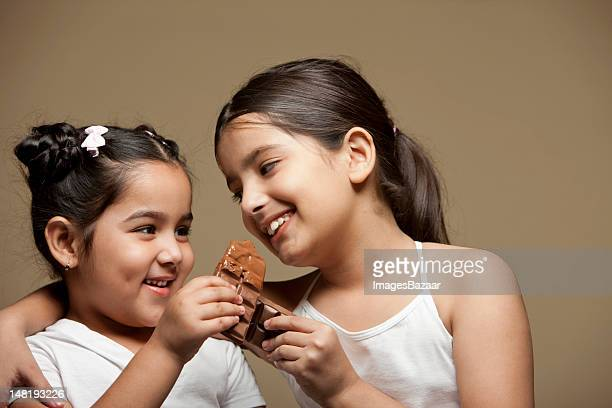 Studio portrait of two sisters (6-11) eating chocolate