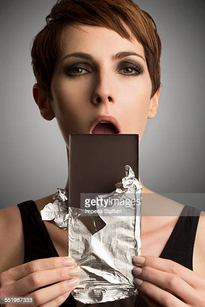 Studio portrait of woman holding up dark chocolate bar to mouth