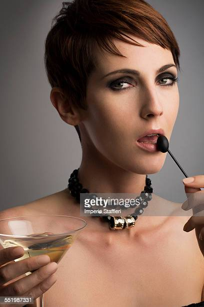 Studio portrait of woman looking sideways holding black olive cocktail stick to her lips